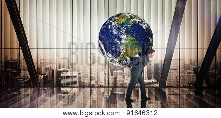 Businessman carrying the world against room with large window looking on city