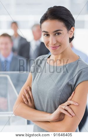Smiling businesswoman looking at camera during conference in meeting room