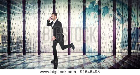 Businessman running on the phone against global business graphic in blue
