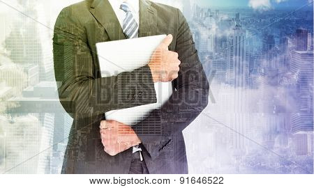 Businessman holding his laptop tightly against room with large window looking on city