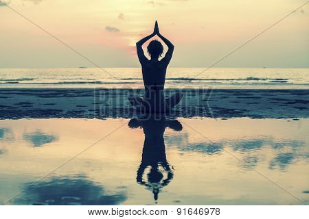 Yoga woman sitting on sea coast at sunset, silhouette, reflection and the sky in soft colours.