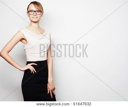Business, finance and people concept:  young  business woman wearing glasses. Over grey background.