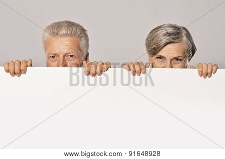 Old age couple holding blank banner