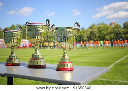MOSCOW - MAY 14, 2014: Three Cups for winners of the International football tournament Cup of Victory in front of a football field and teams at the Spartakovets stadium in Moscow