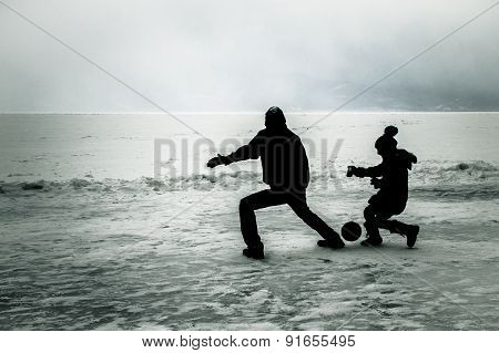 Boys playing football on frozen lake