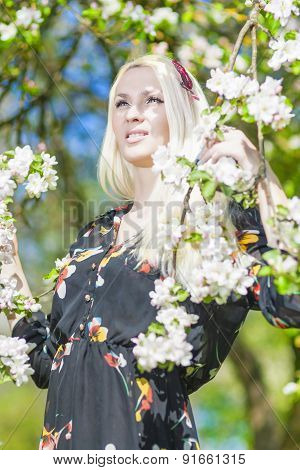 Beauty Concept:portrait Of Beautiful Blond Female Standing In Park By Blooming Tree And Relaxing.