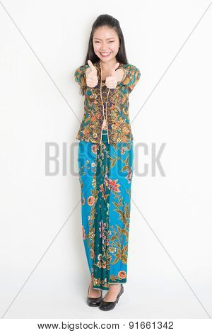 Full length portrait of Southeast Asian woman in batik dress thumbs up standing on plain background.