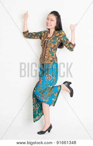 Full length portrait of Southeast Asian woman in batik dress thumbs up, cheering and jumping around on plain background.