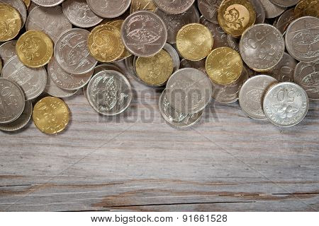 Top view coins on old wooden desk with copy space on bottom.
