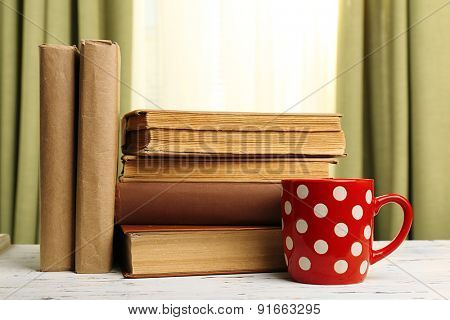 Books and cup on wooden table, on curtains background