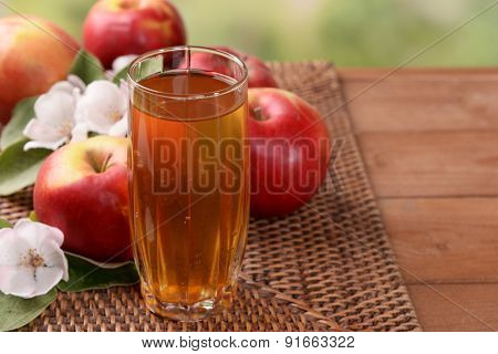 Glass of apple juice and apples on wooden table