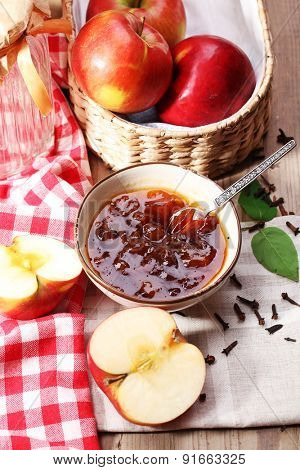 Apple jam and fresh red apples on wooden table close-up