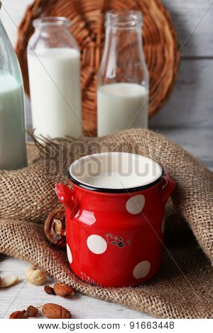 Milk in glassware and walnuts on wooden table with sackcloth, closeup