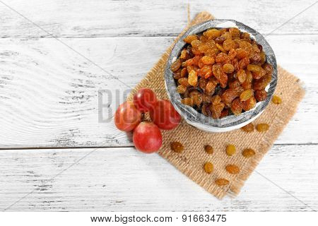 Raisins in small bucket on wooden background