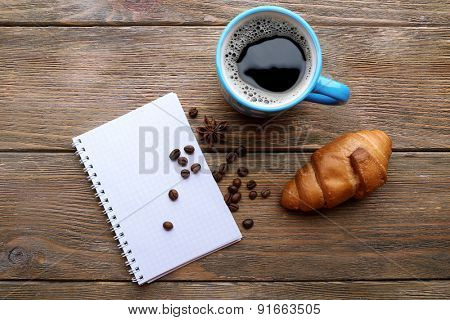 Cup of coffee with fresh croissant and blank sheet of paper on wooden table, top view
