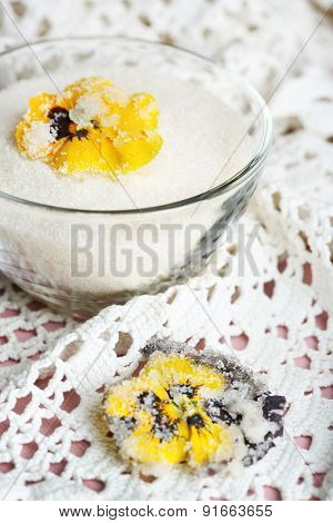 Candied sugared violet flowers, in glass bowl with sugar, on wooden background