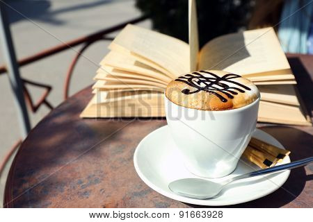 Cups of cappuccino with treble clef on foam  and book on table in cafe