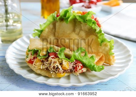 Tasty taco on plate on table close up