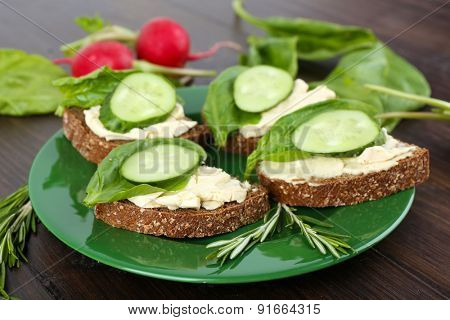 Delicious sandwiches with vegetables and greens on plate close up