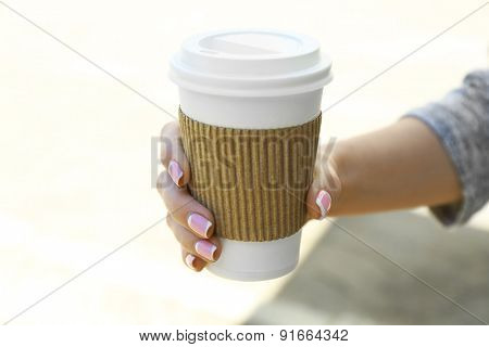 Female hand with paper cup of coffee outdoors, closeup