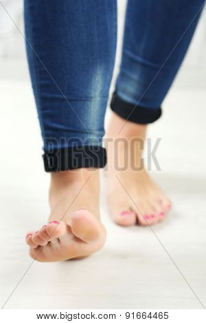 Beautiful female legs on light  floor background