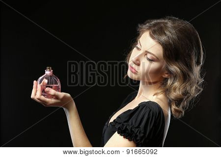 Beautiful woman with perfume bottle on black background