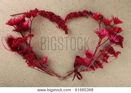 Wildflowers in shape of heart on plywood background