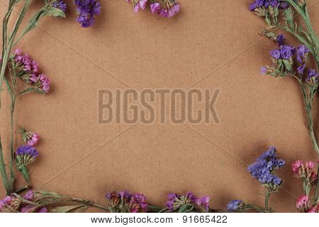 Wildflowers as frame on cardboard background