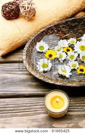 Candles with flowers on plate on table close up