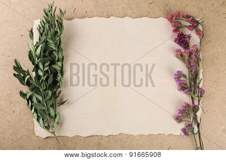Wildflowers on sheet of paper on plywood background