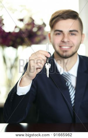 Portrait of businessman with keys in hand in office