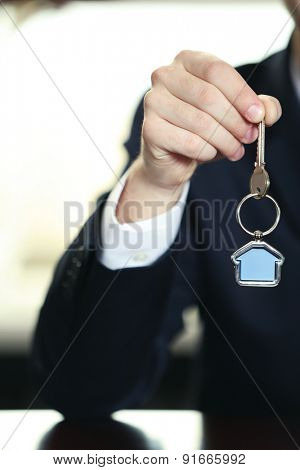 Businessman with keys in his hand in office, closeup
