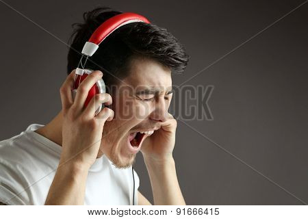 Handsome young man listening to music on grey background