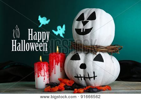 White Halloween pumpkins and candles on wooden table on dark green background