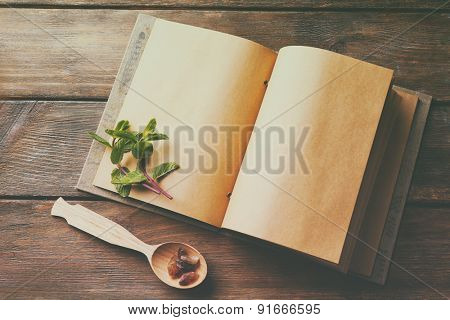 Open recipe book with mint leaves on wooden background