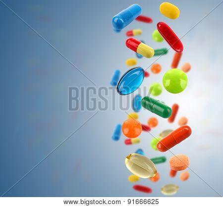 Falling colorful medical pills on blue background