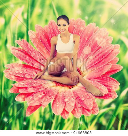 Beautiful young woman sitting on big pink flower on green natural background