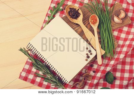 Recipe book page with different herbs on napkin wooden background