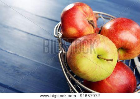 Ripe apples in metal basket on wooden background