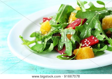 Tasty salad with arugula leaves in plate, closeup