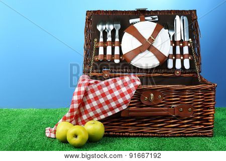 Wicker picnic basket on green grass on blue background