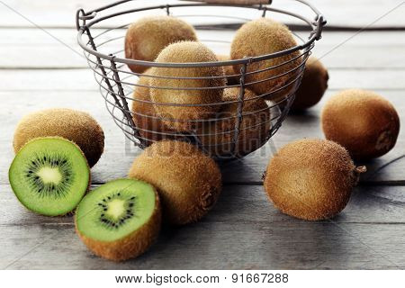 Ripe kiwi in basket on wooden table close-up