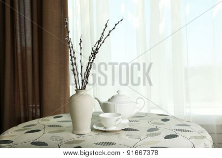 Willow twigs in vase with teapot and cup on table on curtains background