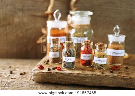 Assortment of spices in glass bottles on cutting board, on wooden background