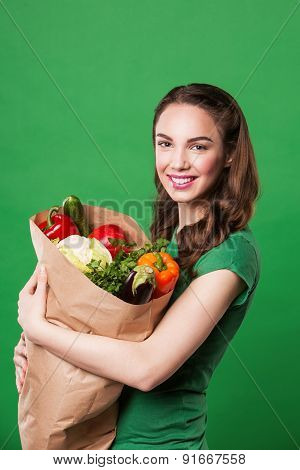 beautiful happy woman holding a grocery bag full of fresh and healthy food. on green background