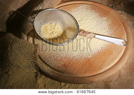 Flour with sieve on wooden cutting board, closeup