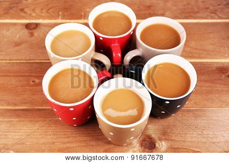 Cups of cappuccino on wooden background