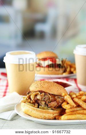 Tasty burger and french fries on plate, on wooden table, on bright background. Unhealthy food concept