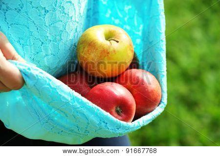 Red apple in hemline of female clothing, closeup