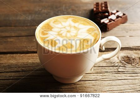 Cup of coffee latte art with chocolate on wooden background
